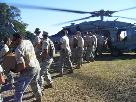photo of soldiers off-loading boxes from a helicopter